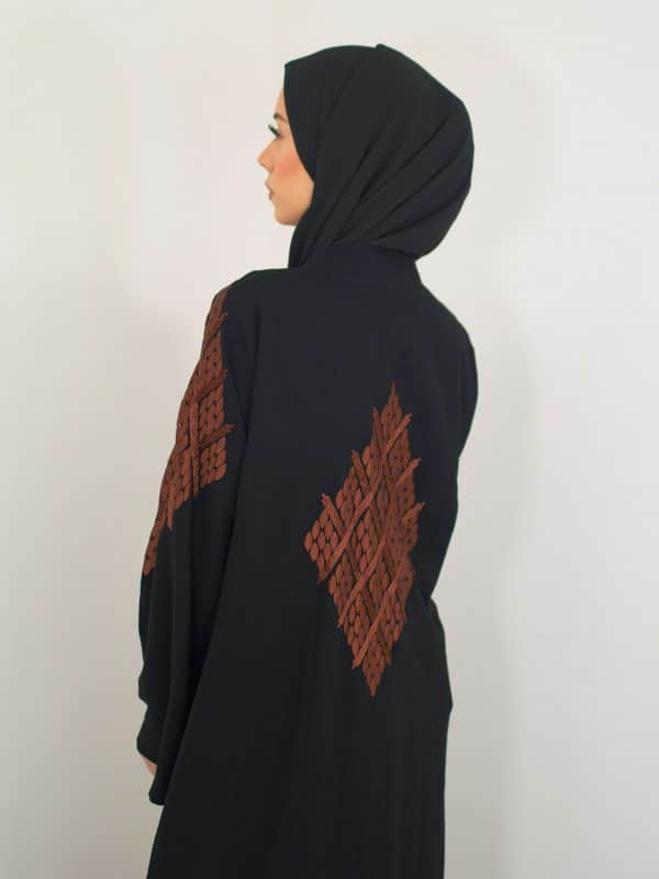 A muslim woman wearing a black open abaya with an arabic symmetry embroidered pattern on the back view