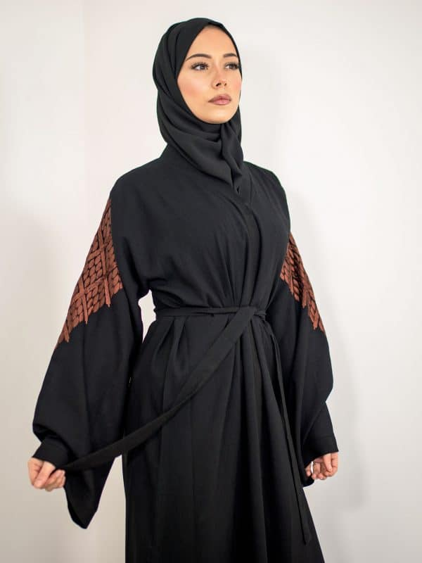A woman wearing a black modest kimono abaya with embroidered sleeves and back